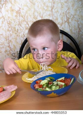 The little boy eats a spaghetti and salad - stock photo