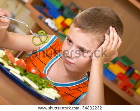 The little boy eats fresh salad on the table - stock photo