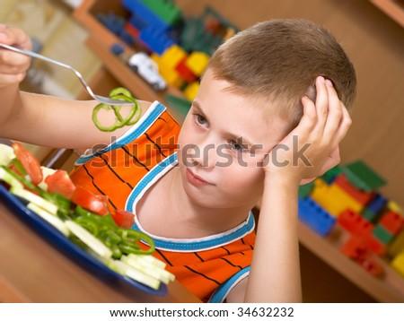 The little boy eats fresh salad on the table - stock photo