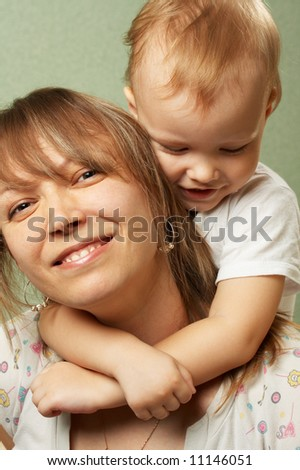The little boy gently embraces the mother for a neck