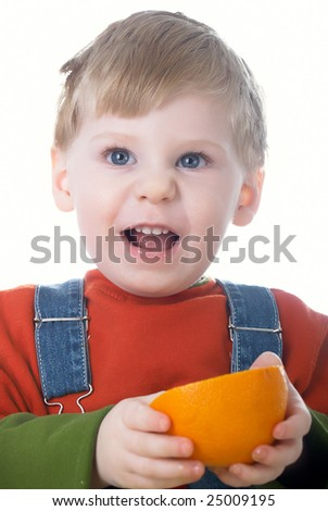 The little boy holds an orange in hands
