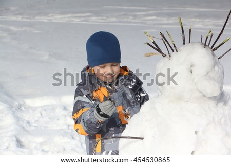The little boy in a color jacket building a snowman in the winter - stock photo