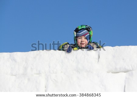 The little boy in a color jacket with a hood at wall top from snow blocks