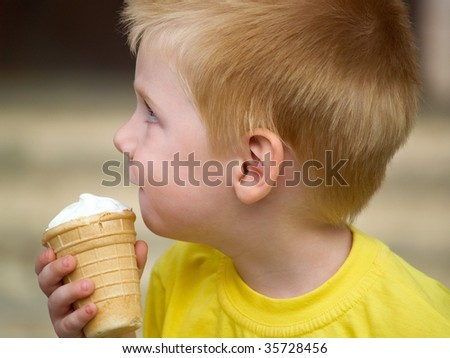 The little boy in a yellow vest eats  ice cream