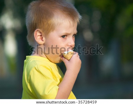 The little boy in a yellow vest eats ice cream - stock photo