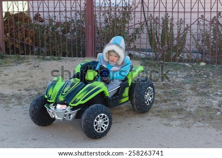 the little boy in warm overalls quickly goes by the car - stock photo