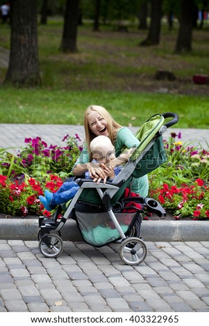 The little boy is biting the hand of his mother. Young mother with two year old son in summer park - stock photo