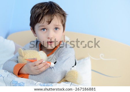 The little boy is sick. He lies in bed. Teddy Bear and thermometerer is in his hand. - stock photo
