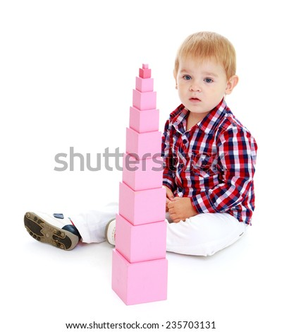 The little boy looked at his folded Red Pyramid.White background, isolated photo. - stock photo