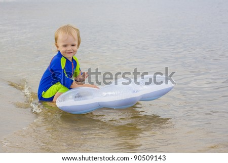 The little boy plays near water - stock photo