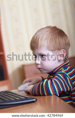 The little boy plays on a computer in a room