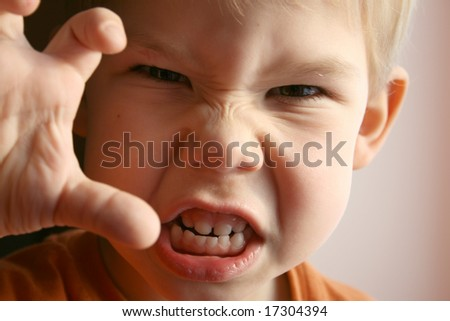 The little boy represents anger. - stock photo