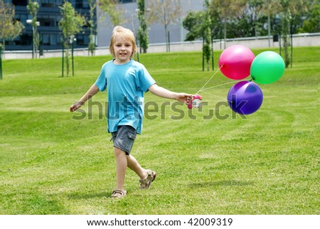 The little boy running on a grass with balloons - stock photo