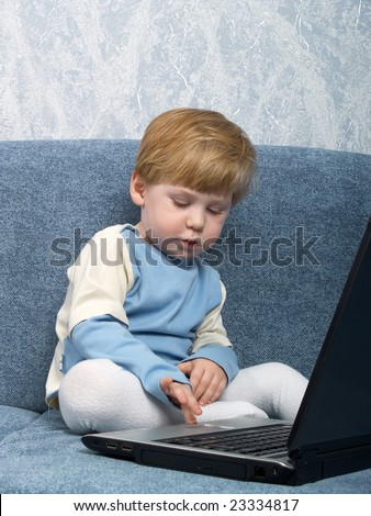 The little boy sits near the closed laptop - stock photo