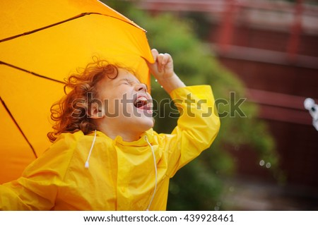The little boy stand in the rain and tongue catches rain drops. He has thrown back the head and has closed eyes. A hand holds an umbrella. - stock photo