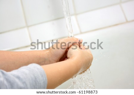 The little boy washes hands in a bathroom