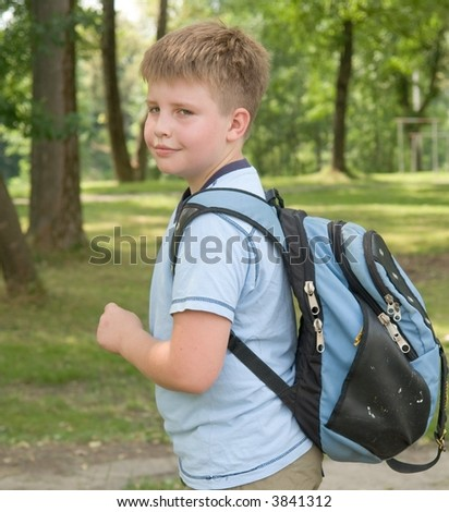 The little boy with a backpack in green park - stock photo