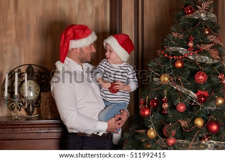 The little boy with dad are decorating a Christmas tree in the house. Happy family. Merry Christmas and Happy New Year.