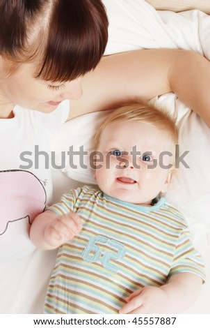The little boy with mum on the bed - stock photo
