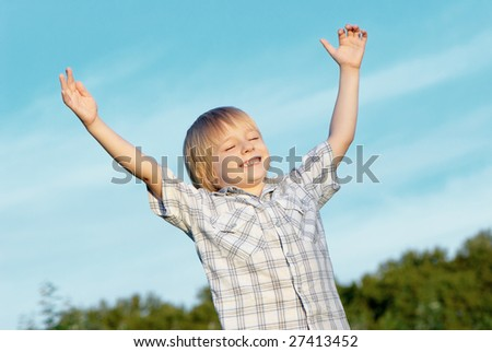 The little boy with stretched hands to sky