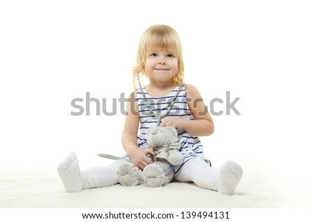 The little clever girl playing the doctor on a white background. - stock photo