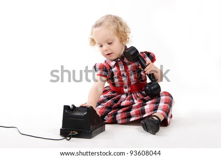 The little curly-haired blonde girl, wearing a checkered dress, talking on the old black phone, calling mom isolated on white. Retro style