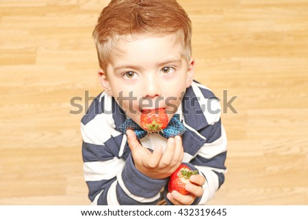 The little cute and handsome boy  wearing classic style clothes and tries to eat the strawberries - stock photo