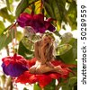 The little elf on a flower in a fairy garden - stock photo