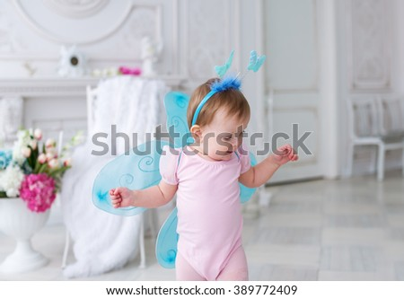 The little fairy with wings in a pink dress. The small child in a suit of the fairy. - stock photo