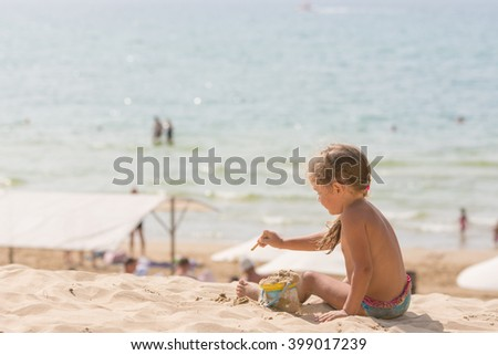 The little five year old girl sitting on the beach and playing with sand and toys on the background of the sea - stock photo
