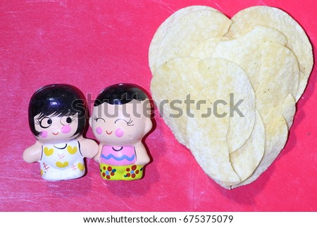 the little girl and boy dolls and potato chip heart on red background