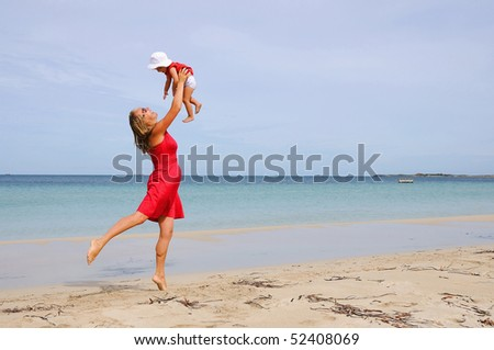 The little girl and mother in a red dress on the beach - stock photo