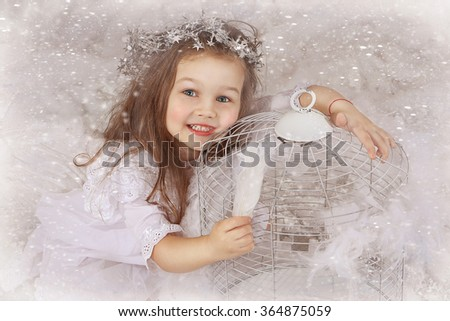 The little girl. Angel. With plumelets in a hand near a decorative cage