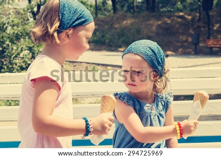 The little girl doesn't want to change ice cream with his sister, selective focus. - stock photo