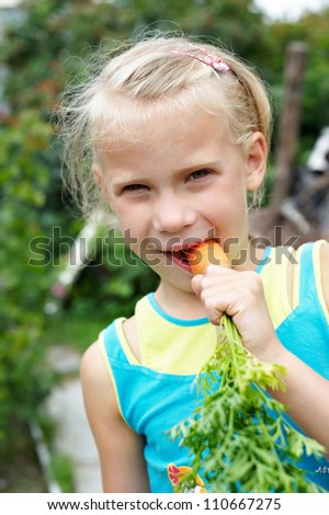 The little girl eating a carrot outdoors
