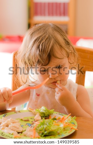 The little girl eating  on the table - stock photo