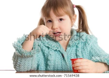 The little girl eats yoghurt - stock photo