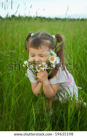 The little girl embraces wild flowers - chamomiles - stock photo