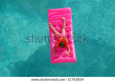 The little girl floats on an inflatable mattress in pool - stock photo