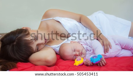 The little girl has fallen asleep on a blanket near mother and toys. Mother and daughter