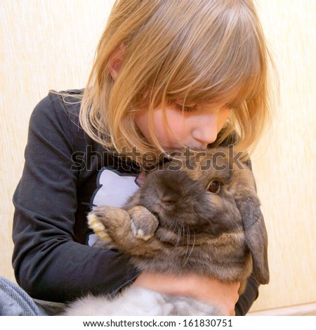 The little girl hugging and kissing rabbit. Love for animals concept. - stock photo