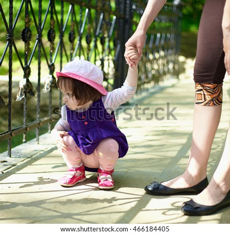 The little girl in a blue dress walking with her mother on the bridge. He sat down and looking at the water.