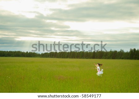 The little girl in a dress runs on a meadow - stock photo