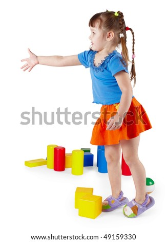 The little girl in a dress with toys on a white background