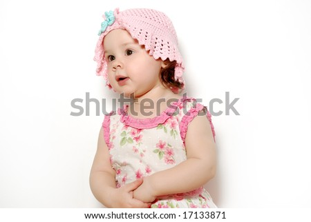 The little girl in a pink hat on white background