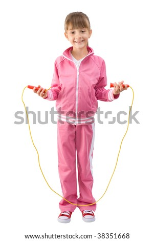 The little girl in a pink sports suit jumps through a jumping rope - stock photo