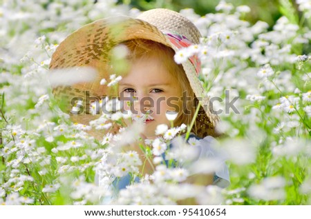 The little girl in a straw hat among the daisies - stock photo
