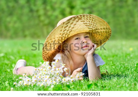 The little girl in hat lying on the lawn - stock photo