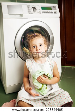 The little girl in the apron . Laundry , washing machine