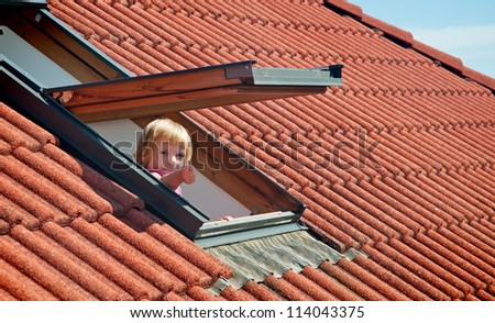 The little girl in the roof window . - stock photo